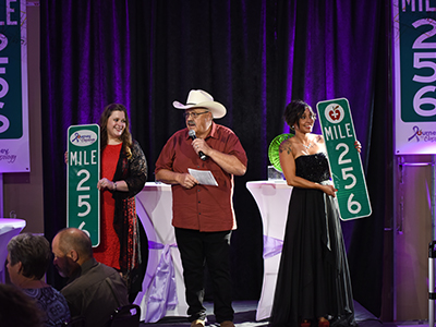 Image of Nenow Auction auctioning off Mile Marker 256 signs at the Journey to Mile 256 cancer fundraiser.