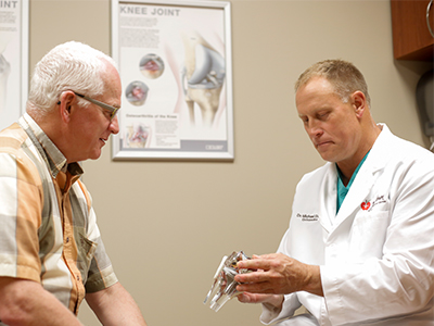 JRMC Orthopedic Surgeon, Dr. Michael Dean, examines a patient at the JRMC Carrington Clinic.